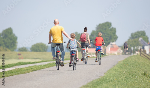Fotografie, Obraz Cyclists cycling on a dyke