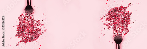 Obraz na plátne Banner with professional cosmetic makeup brushes with explosion of shiny pink colorful sparkles on pastel pink background with copyspace for your text