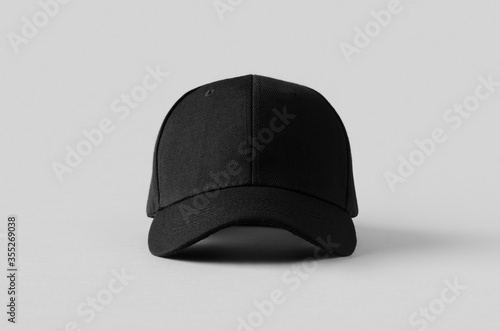 Fototapeta Black baseball cap mockup on a grey background, front view.