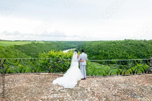 Newlyweds holding hands hugging at white sandy tropical caribbean beach landscap Fototapeta