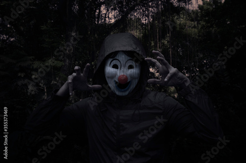 Wallpaper Mural Scary evil clown wear jacket standing over spooky dark forest with tree, leaves