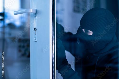 Wallpaper Mural Robber in black balaclava cracking door with metal picklock