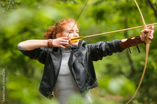 Foto Sporty young woman practicing archery outdoors