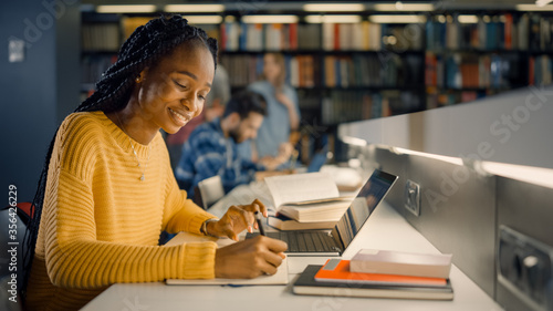 Foto University Library: Gifted Black Girl uses Laptop, Writes Notes for the Paper, Essay, Study for Class Assignment