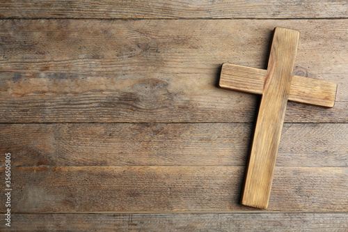 Fototapeta Christian cross on wooden background, top view with space for text