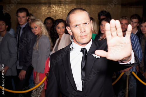 Portrait of bouncer with arm outstretched outside nightclub Fototapeta