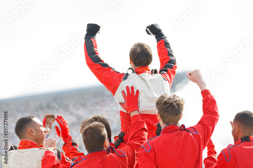 Fotografering Racer and team cheering on track