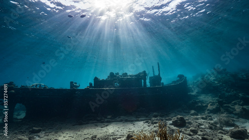 Fotografie, Obraz Ship wreck Tugboat in  shallow water of coral reef in Caribbean sea / Curacao