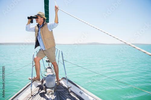 Stampa su Tela Older man looking out binoculars on edge of boat