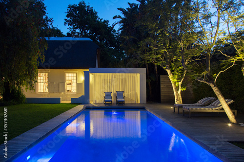 Canvas Lawn chairs on wooden deck by illuminated swimming pool at night