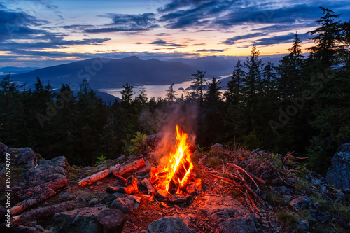 Billede på lærred Warm Camp Fire on top of a mountain with Beautiful Canadian Nature Landscape in background during a colorful Sunset