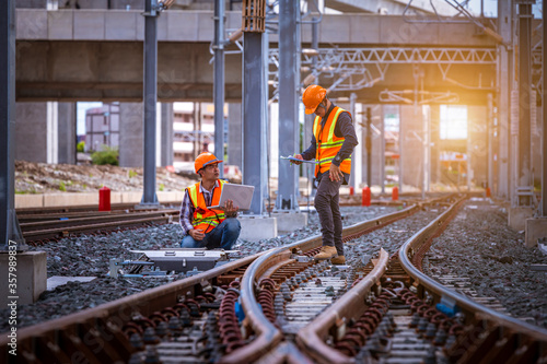 Fotografia Engineer under inspection and checking construction process railway switch and checking work on railroad station