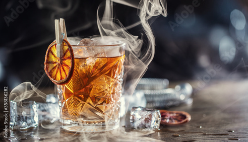 Stampa su Tela Smoked old fashioned rum cocktail with cubes of ice around on a dark background