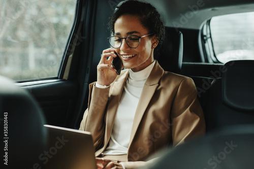 Obraz na plátne Businesswoman working inside a cab on the way to work
