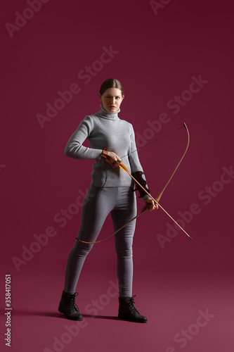 Stampa su Tela Beautiful woman with crossbow on color background