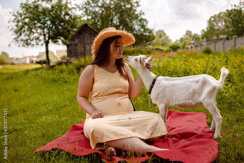 Canvas Print a woman with her goat sits on the grass and feed it