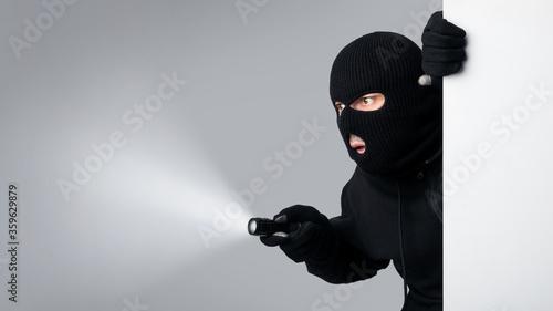 Fotografiet Masked villain peeking out white blank board