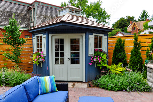 Fotografia Beautiful professionally designed luxury garden oasis features extensive hardscaping with patio, seat wall outdoor furniture and high end shed