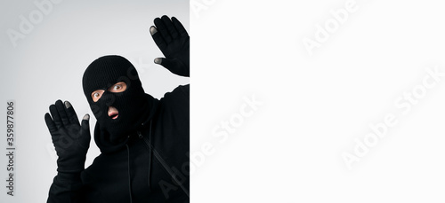 Photo Masked thief with raised arms isolated on white wall