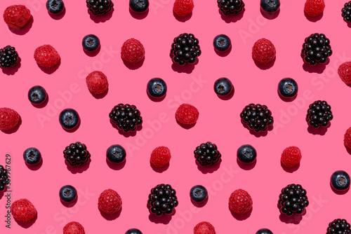 Fototapete Pattern of raspberries, blueberries and blackberries against pink background