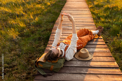 Fotografia Woman naturalist orange overalls makes selfie on the phone, resting lying on backpack on wooden path through peat bog swamp in wildlife national park at sunset
