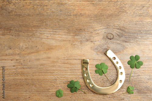 Wallpaper Mural Clover leaves and horseshoe on wooden table, flat lay with space for text