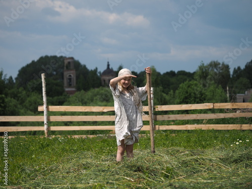 Life of a child in the village. Children's work in the hay field Fototapeta