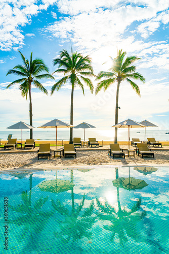 Fototapeta Beautiful luxury umbrella and chair around outdoor swimming pool in hotel and re