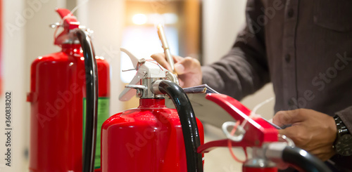 Slika na platnu Fire fighter are checking fire extinguishers tank in the building concepts of fi