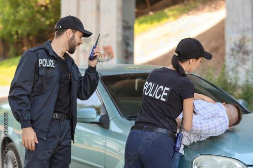 Obraz na płótnie Police officers arresting criminal outdoors