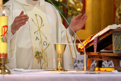 Photo Chalice on the altar and priest celebrating mass in the background