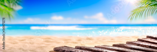 Fotografia Wooden Boardwalk On Beach With Sunny Sky And Palm Leaves - Abstract Travel Backg