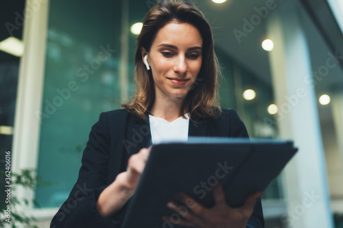 Leinwand Poster Successful female banker using tablet and wireless earphones outdoors near his o
