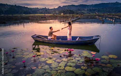 Couple In Boat On Lake During Sunset