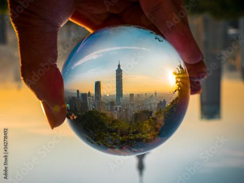 Fototapeta premium Przycięta Ręka Trzymająca Kryształową Kulę Z Odbiciem Tajpej 101 W Mieście Podczas Zachodu Słońca