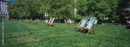 Canvastavla Panoramic View Of Deck Chairs On Field In Public Park
