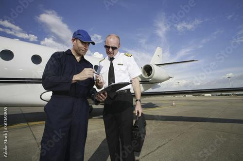 Fotografija Plane engineer and pilot looking at document on clipboard