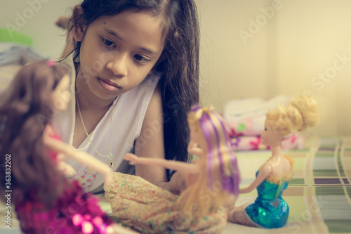 Fotografia Little Girl Is Playing Dolls On Bed In Holiday.