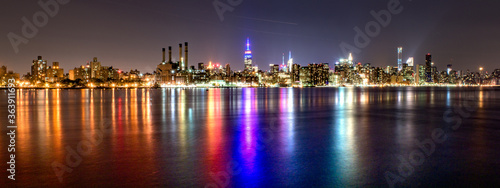 Fotografering Panoramic Shot Of East River By Illuminated Modern City Against Clear Sky At Nig