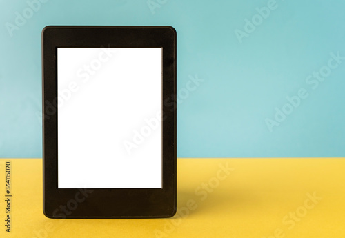 Carta da parati A modern black electronic book with a white blank empty screen on yellow and blu