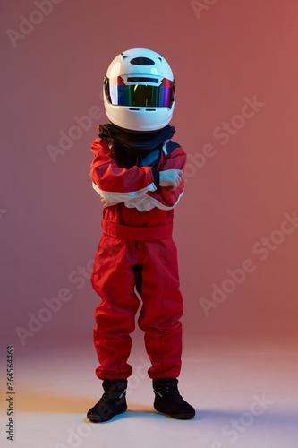 Fototapeta Cool boy child racer in helmet, racing suit, standing in neon light