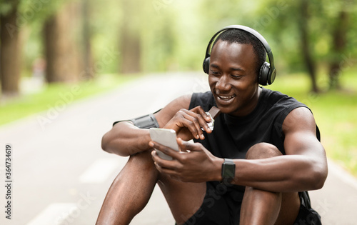 Photo Positive black sportsman eating protein bar while resting