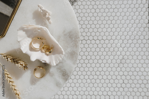 Leinwand Poster Minimal fashion composition with golden earrings in seashell on marble table with mirror and wheat stalks