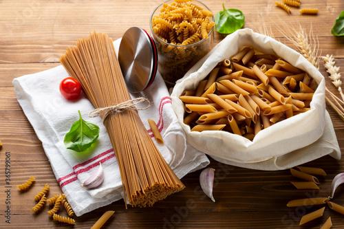 Whole wheat spaghetti and penne on wooden table Fototapeta
