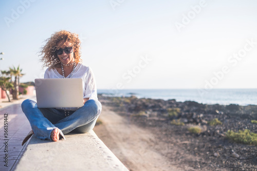 Fotografie, Obraz Happy lifestyle digital nomad young cheerful woman work outdoor with laptop comp