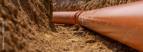 Fotografie, Obraz Plastic pipes in the ground during the construction of a building, bunner with c