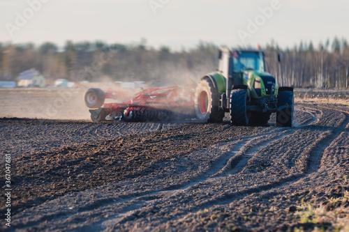 Obraz na plátně Tractor with a disc harrow system harrows the cultivated farm field, process of
