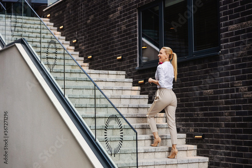 Murais de parede Gorgeous blond smiling fashionable lady ascending the stairs and talking on the phone