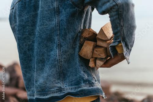 Obraz na plátne cropped view of man in denim jacket holding firewood