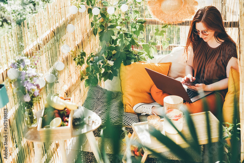 Photo Cheerful young woman wearing brown blouse and sunglasses working on modern laptop sitting on the balcony with lemonade on sunny day